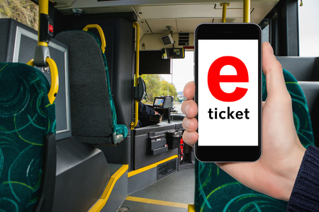 Hand with phone on the background of the city bus. The idea for the app purchase an e-ticket for public transport Standard-Bild