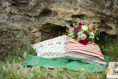 There are stone colored cushions. bouquet style boho, rustic. decorations for a wedding outdoors,in the countryside.