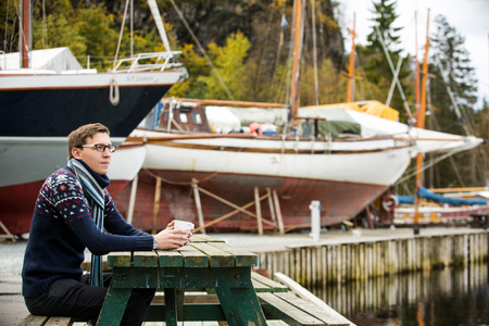 Yachtsman with coffee sitting on a pier on a background of yachts Standard-Bild