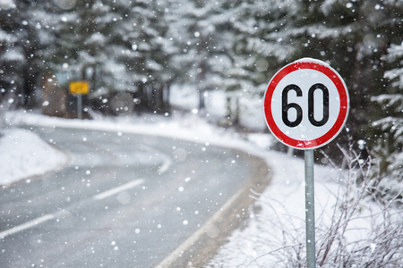 Mountain winter road with a speed limit sign