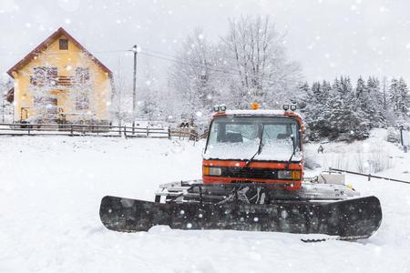 Red snowcat bulldozer on the mountains ski resort