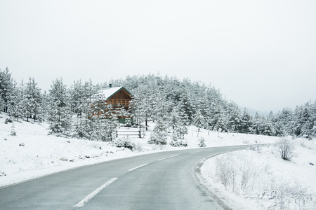 Mountain winter road goes through the village 스톡 콘텐츠