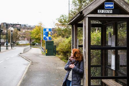 Meisje op een bushalte in Europa Stockfoto