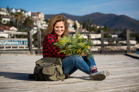 Happy girl traveler sits on a wooden pier and holds a bouquet of flowers of mimosa in hands. Next to the woman is a backpack. Sea and mountains on the horizon. Professional lighting.
