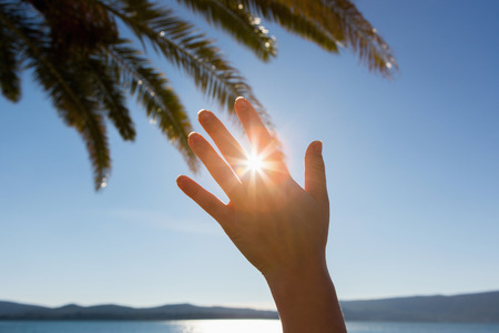 The woman shields the sun with her hand. In the background a palm tree
