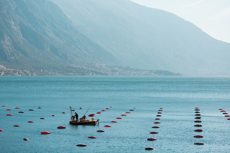 Two workers of mussel and fish farm float on a raft and service nets