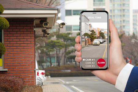 Hand met telefoon. Op het scherm interface van afstandsbediening bewakingscamera