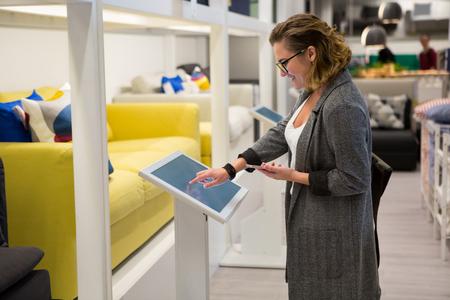 Mujer con teléfono configurando muebles en el dispositivo de autoservicio en la tienda Foto de archivo