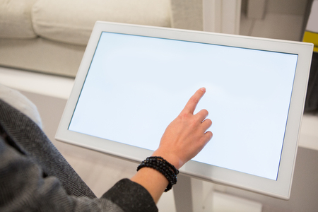 A woman touching the screen of self service device in the store. Banco de Imagens - 100205315
