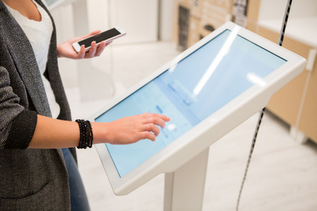 A woman touching the screen of self service device in the store.