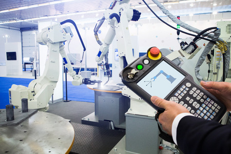 Engineer with teach pendant device. Programming robot with robotic arm. Smart factory