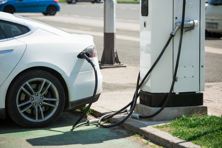 The electric car is charging at the station. Transport network for autotravels. Stock Photo