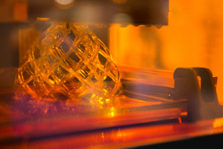 A stereolithography 3d printer in the laboratory prints a structure from a photopolymer. Creating scaled model by UV polymerization.