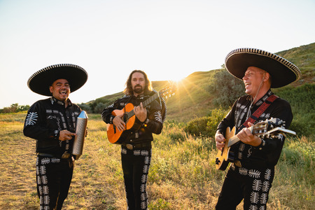 Mexican musicians mariachi in traditional costumes at sunset