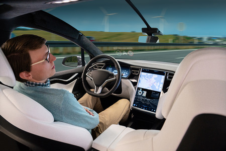 A man sleeps while his car is driven by an autopilot. Self driving vehicle concept Stockfoto