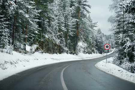 Winter mountains road with sign of snow