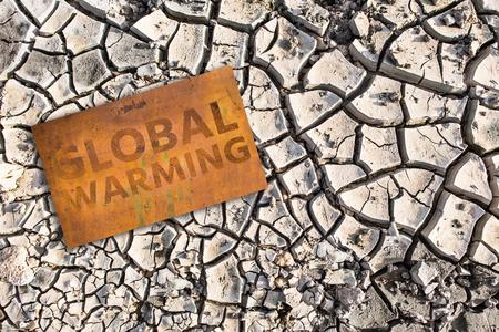 Rusty sign with text Global warming.  Climate change concept.