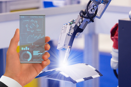 Engineer uses a futuristic transparent smartphone to control robot in a smart factory. Smart industry 4.0 concept. Фото со стока - 120948456