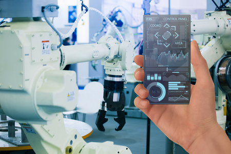 Engineer uses a futuristic transparent smartphone to control robot in a smart factory. Smart industry 4.0 concept.