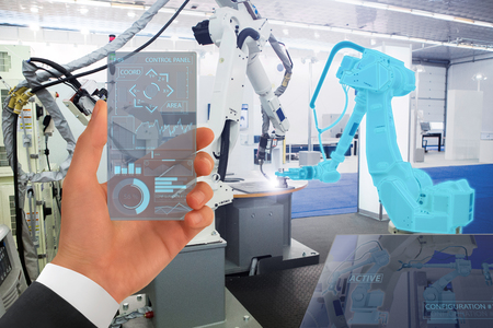 Engineer uses a futuristic transparent smartphone to control robots in a smart factory. Smart industry 4.0 concept. Imagens