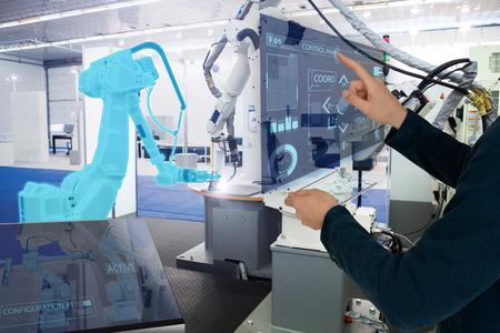 The engineer uses a futuristic projection touch screen to control robots in a smart factory. Smart industry 4.0 concept Banco de Imagens