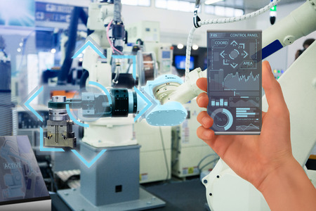 Engineer uses a futuristic transparent smartphone to control robots in a smart factory. Smart industry 4.0 concept. Zdjęcie Seryjne