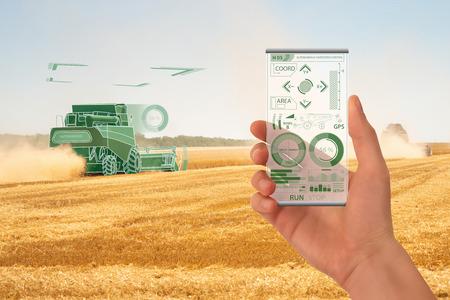 Farmer uses a futuristic smartphone to control autonomous harvester. Smart farming concept