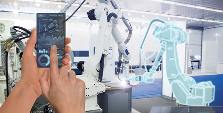 Engineer uses a futuristic transparent smartphone to control robots in a smart factory. Smart industry 4.0 concept. Фото со стока