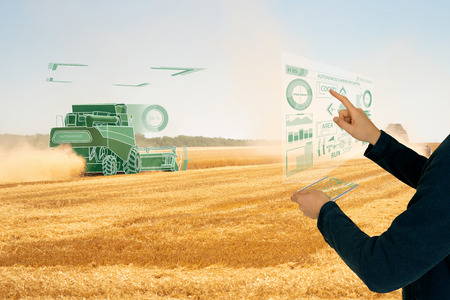 Farmer uses a futuristic projection touch screen to control autonomous harvester. Smart farming concept
