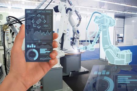 L'ingegnere utilizza uno smartphone trasparente futuristico per controllare i robot in una fabbrica intelligente. Concetto intelligente di industria 4.0.