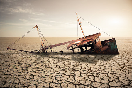 Rusty ship in a dried ocean. Concept of global warming and climate change Фото со стока
