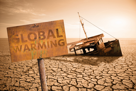 Rusty sign with text Global warming and old ship in a dried ocean.  Climate change concept.