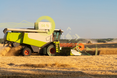 A modern combine harvester harvests wheat using a head-up display and the Internet of things in agriculture.