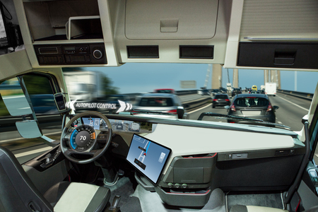 Self driving truck with head up display on a road. Inside view. Фото со стока