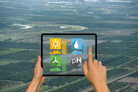 A farmer is holding a tablet on the background of an agricultural land. Smart farming and digital agriculture concept Фото со стока