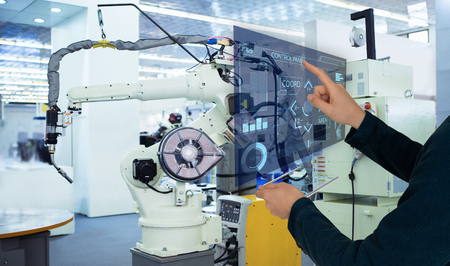 The engineer uses a futuristic projection touch screen to control robots in a smart factory. Smart industry 4.0 concept Фото со стока - 120948515
