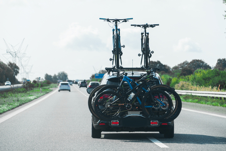 Car with bikes on the hitch-mounting bike rack on the highway