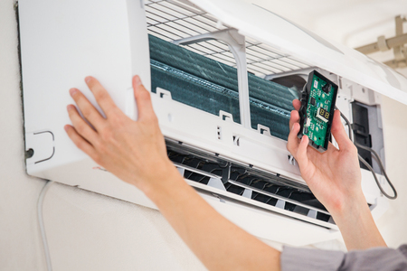 Service man is cleaning, repair and maintenance of air conditioner Фото со стока