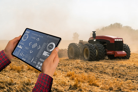 A farmer with digital tablet controls an autonomous tractor on a smart farm