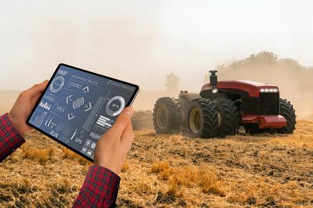 Un agricultor con tableta digital controla un tractor autónomo en una granja inteligente