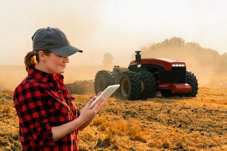 La agricultora con tableta digital controla un tractor autónomo en una granja inteligente