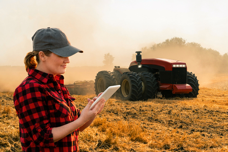 Woman  farmer with digital tablet controls an autonomous tractor on a smart farm 免版税图像