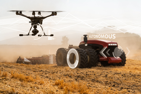 Autonomous tractor and drone working on the field. Smart farming