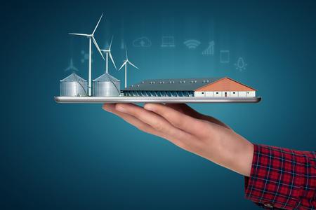 Farmer sostiene una tableta con una granja inteligente moderna que utiliza energía renovable. Transformación digital en agricultura.