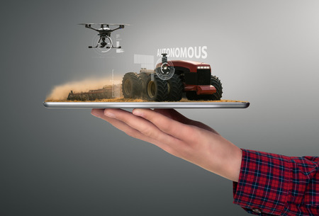 Farmer holding a tablet with autonomous tractor and drone. Smart farming