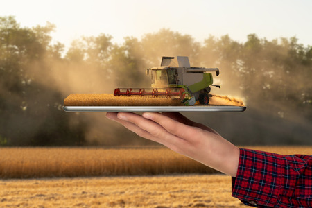 Farmer holding a tablet with a combine harvester. Augmented reality and digital transformation in agriculture. Smart farming concept Imagens