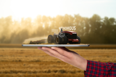 Farmer holding a tablet with autonomous tractor. Smart farming
