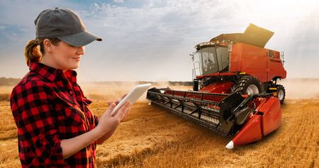 Woman farmer with digital tablet on a background of harvester