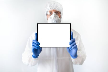 Medical doctor in protective suit with a digital tablet