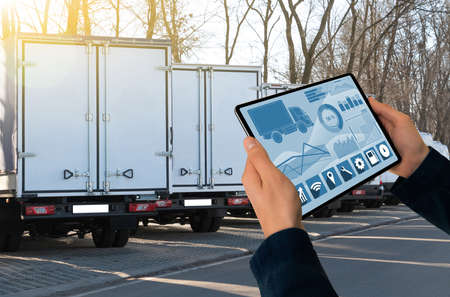 Manager with a digital tablet on the background of trucks. Fleet management
